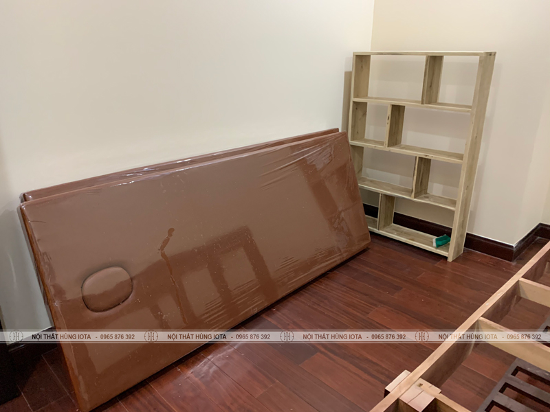 Đệm giường spa màu nâu và kệ trưng bày sản phẩm spa