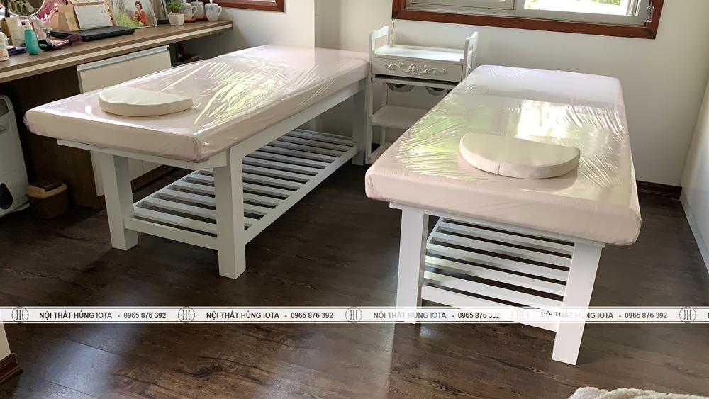Giường spa màu trắng và xe đẩy có bát nước